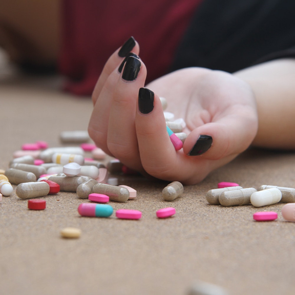 Woman unconscious on floor, holding a pile of pills
